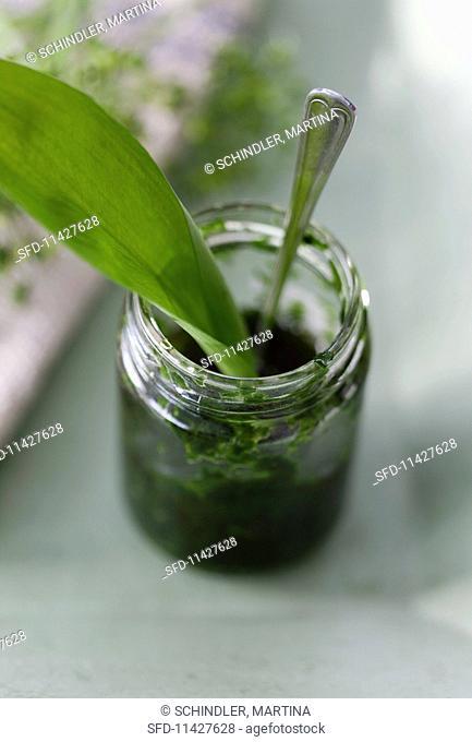 Wild garlic pesto in a jar with a wild garlic leaf