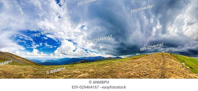 Panorama mountain ranges of the Carpathians against the backdrop of cumulus and storm clouds