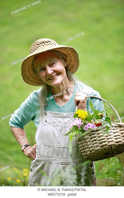 Senior woman with straw hat looking into camera with basket of flowers