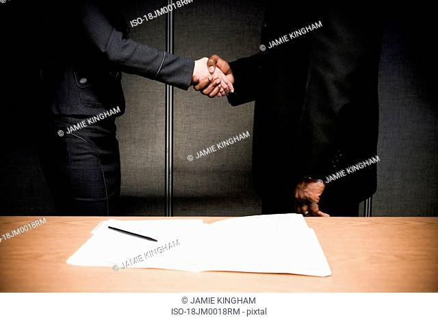 Man and woman in suits shaking hands