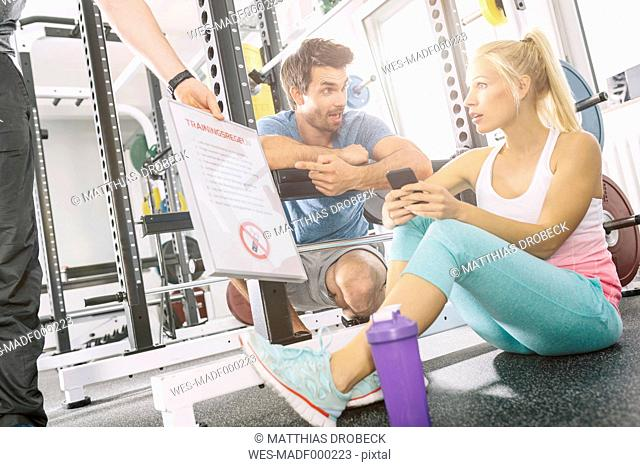 Young couple astonished about mobile phone prohibition at gym