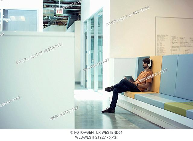 Young businessman using headphones and digital tablet, sitting on bench with