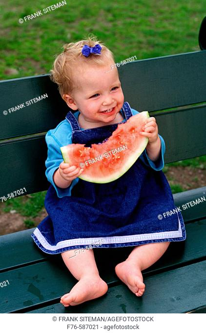 One year old baby girl eating watermelon
