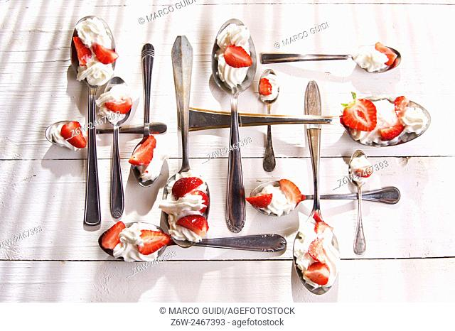 Presentation of the strawberries with cream spoons on various