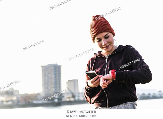 Sportive young woman at the riverside in the city with smartphone and smartwatch