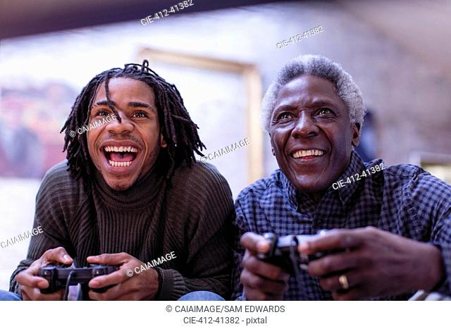 Enthusiastic grandfather and grandson playing video game