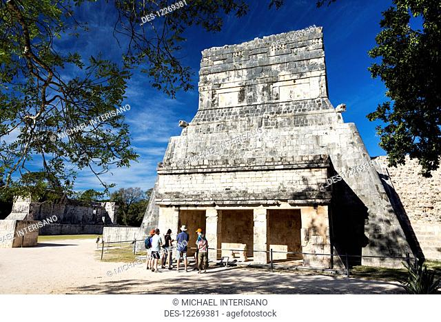 Ancient Mayan Temple framed by trees with tourist on tour and blue sky; Chichen Itza, Yucatan, Mexico