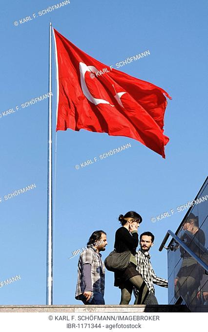 Young people in European dress walking under the Turkish flag, Taksim Square, Beyoglu, Istanbul, Turkey