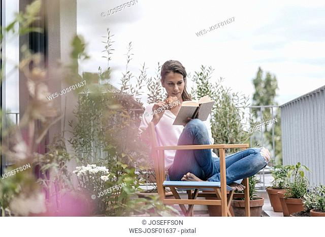 Woman eating croissant and reading book on balcony