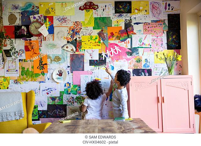 Toddler brother and sister hanging art on wall