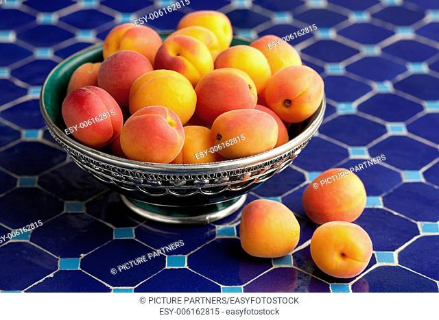 Ripe apricots in a Moroccan bowl on a blue mosaic table