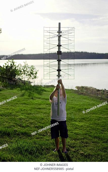 A boy holding a digital television aerial, standing by the sea, Sweden