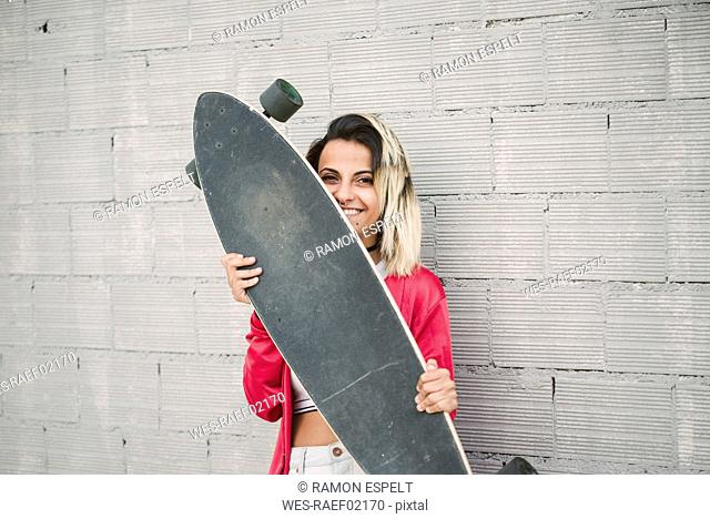 Portrait of a young woman with her long board, in front of a wall
