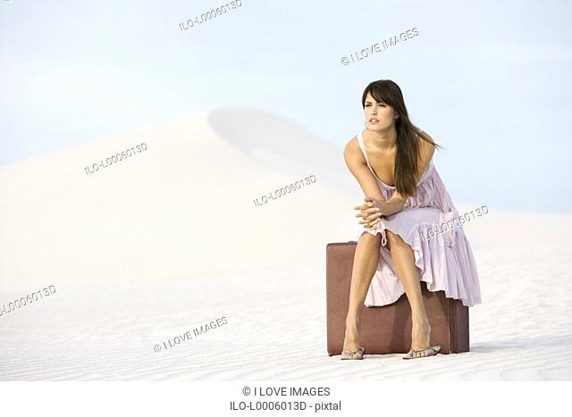 A young woman sitting on a suitcase in the desert