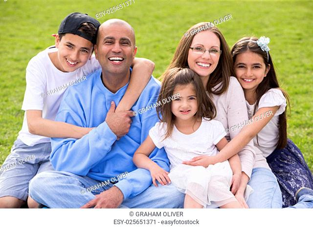 A portrait of a mixed ethnicity family, mum and dad have three cute children between the ages of 4 to 10. They are sitting down and smiling happily at the...