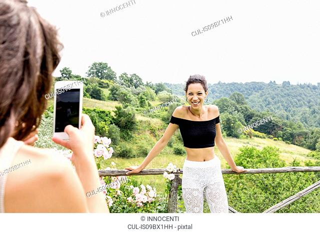 Woman taking photo of friend with view of Città della Pieve, Umbria, Italy