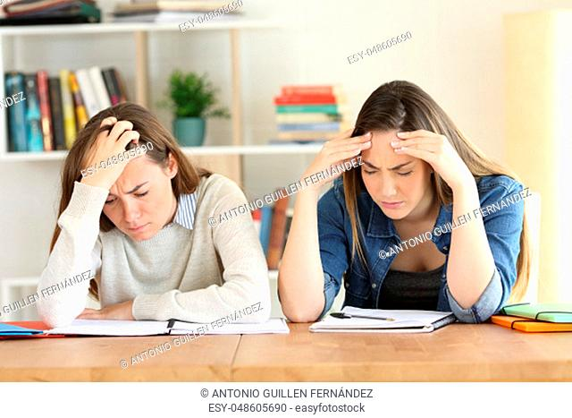Front view of two fatigued students studying hard at home