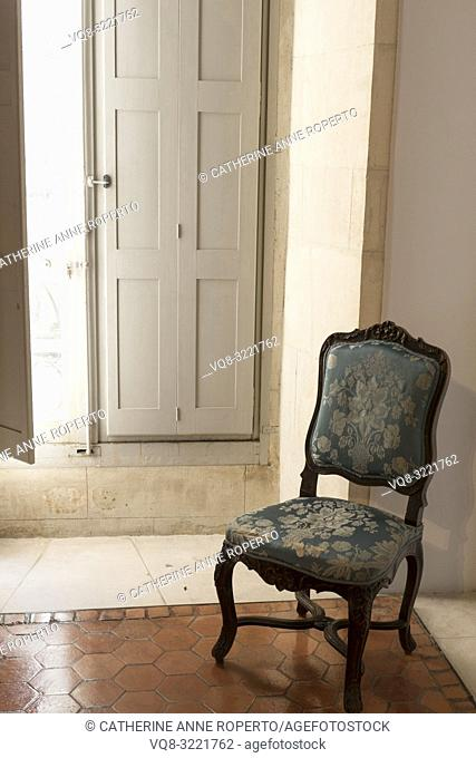 Antique, tattered silk taffeta Cinderella chair, on traditional shiny hexagonal terracotta tiles, illuminated by the midday sun