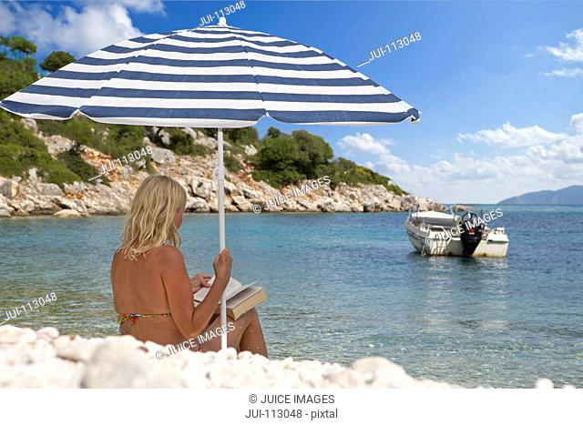 Woman reading book under striped beach umbrella on sunny beach