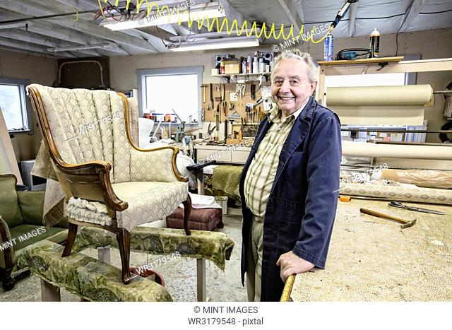 Caucasian senior male upholsterer working on a chair in his garage shop