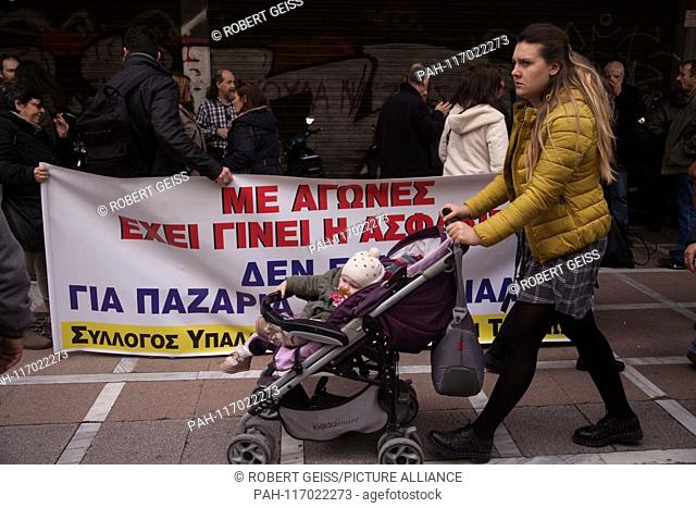 Mother with child in front of protest by employees of Social Security Sector against austerity measures. Demanding increase of personal