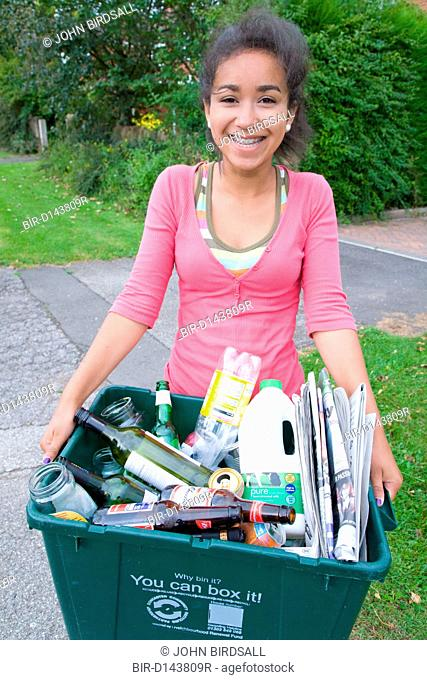 Teenage girl carrying curb side recycling collection box out onto the pavement ready for collection