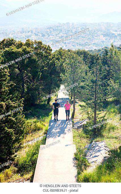 Young man and woman running in park, Split, Dalmatia, Croatia