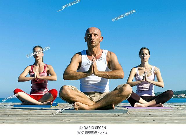 People practising yoga on boardwalk, lotus pose
