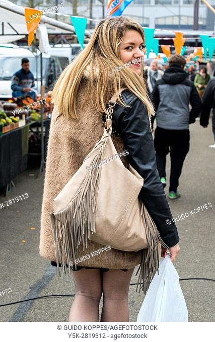 Tilburg, Netherlands. Young adult woman buying her groceries at the weekly down town saturday market