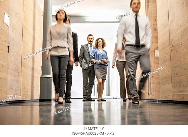 Business people standing in busy hallway