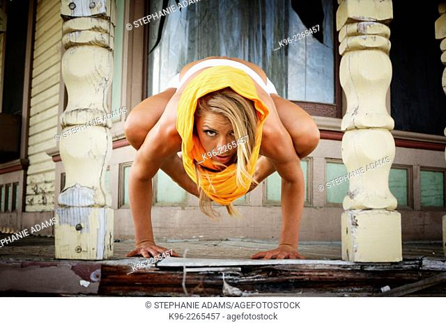 Female on old porch of a house holding a difficult yoga pose