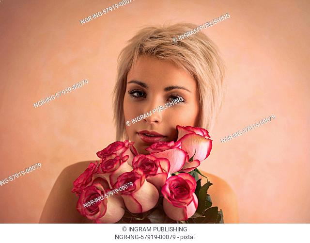 Young beautiful woman holding bouquet of pink roses. She is very satisfacted. Valentine's day or international women's day celebration