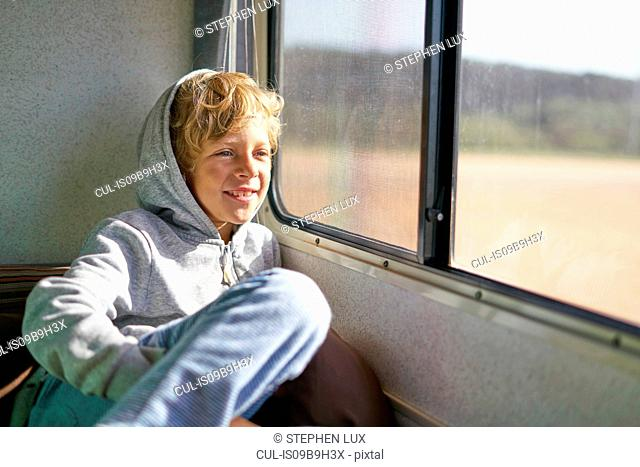 Boy sitting in campervan looking out of window, Polonio, Rocha, Uruguay, South America
