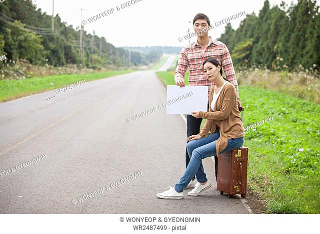Young tired couple with a carrier trying to hitchhike on a road