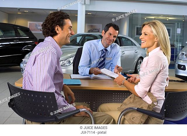 Car salesman and couple sitting at desk in large car showroom, woman handing over paperwork, smiling