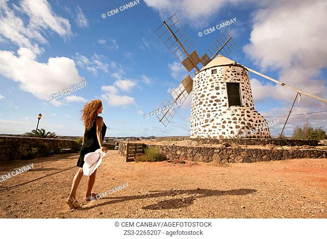 Woman posing in front of the windmill near Tefia, La Oliva, Fuerteventura, Canary Islands, Spain, Europe