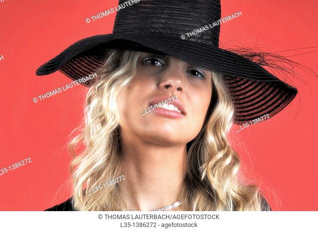Young blonde woman in a black hat against a red background