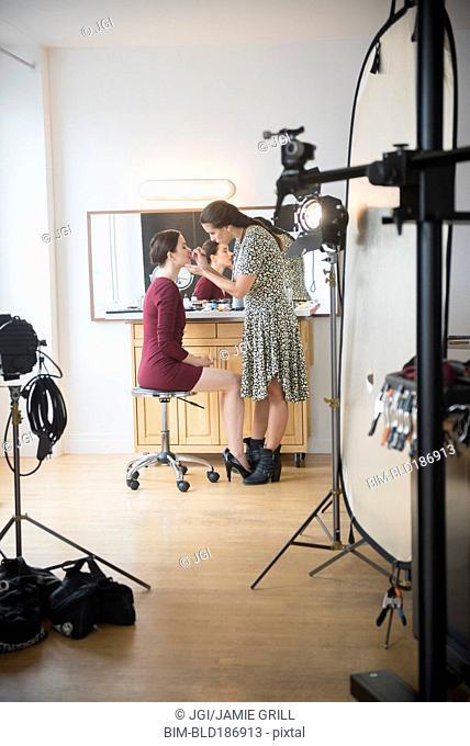 Model having makeup applied by stylist