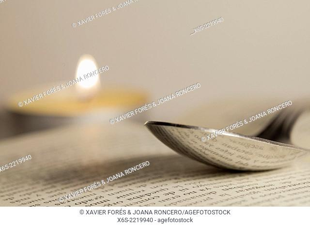 Spoon, candle and book