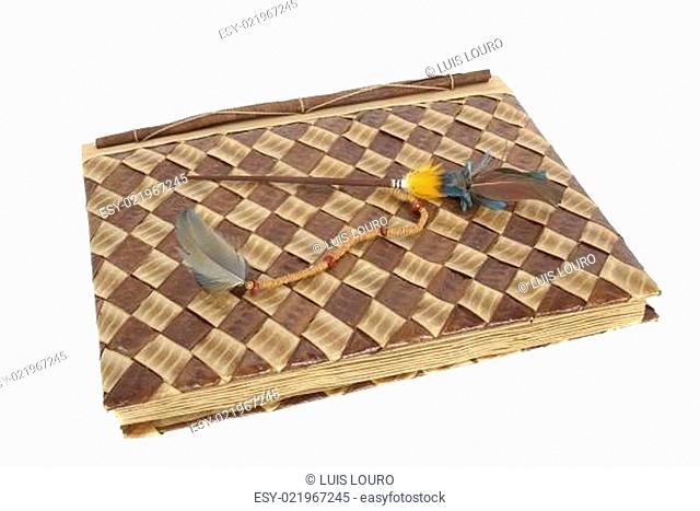 Old photo album with etnic feathers isolated against a white background
