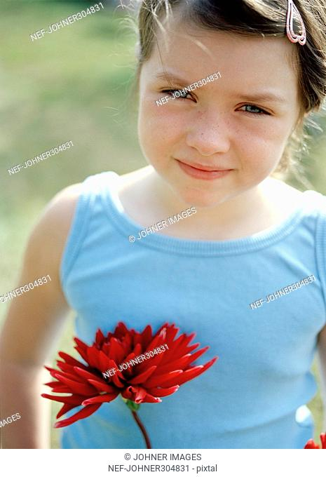 Portrait of a girl holding a red flower