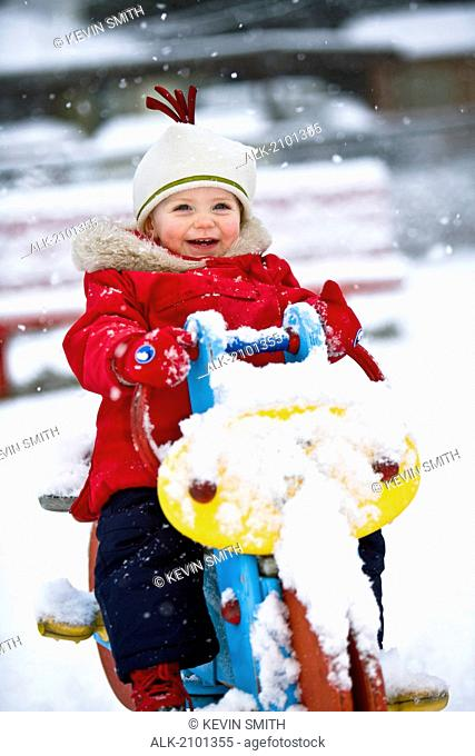 Infant Girl Riding Snowcovered Playground Equipment At An Anchorage Park During Winter In Southcentral Alaska