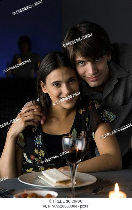 Portrait of couple at restaurant, holding hands, smiling at camera