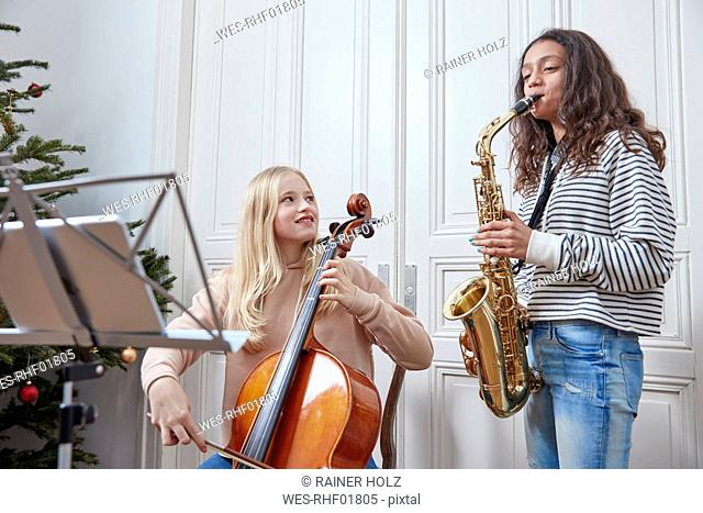 Two girls playing cello and saxophone at Christmas tree