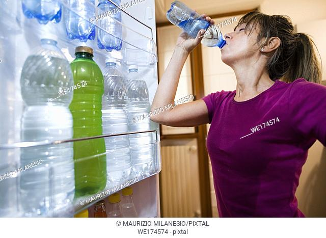Sweaty woman drinking water, point of view from inside the open fridge, in the door numerous bottles
