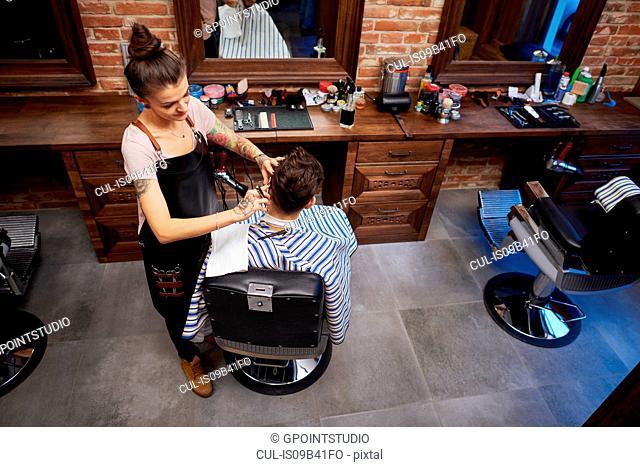 Hairdresser shaving customer's hair with straight razor