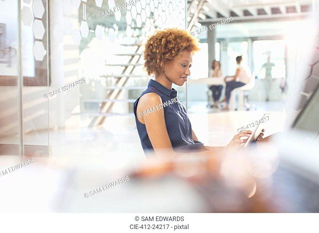 Woman using digital tablet in office, colleagues in background