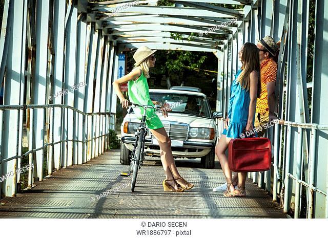 Croatia, Dalmatia, Young people talking on footbridge, car in background