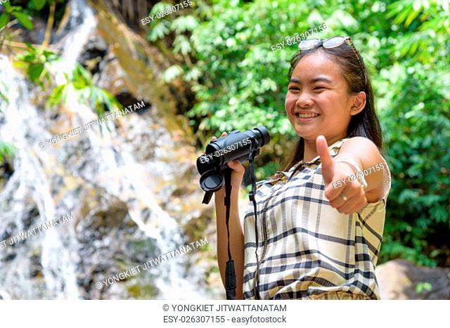 Beautiful young girl hiking is using binoculars look for birds smiled and raised a thumb to the camera in tropical forest near the waterfalls in Thailand