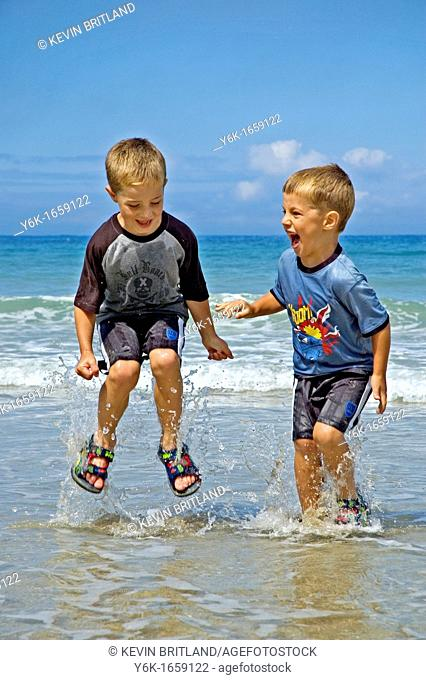 two little boys splashing in the sea in cornwall, uk